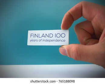 Finland celebrating 100 years of independence in 6th December 2017. Fingers holding white card with Finland 100 years of independence text. Suomi sata