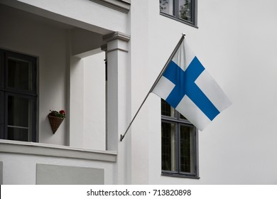 Finland flag. Finnish flag displaying on a pole in front of the house. National flag of Suomi Finland waving on a home hanging from a pole on a front door of a building.Liputuspäivä