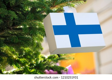 Finland flag printed on a Christmas gift box. Printed present box decorations on a Xmas tree branch. Christmas shopping in Suomi Finland, sale and deals concept.