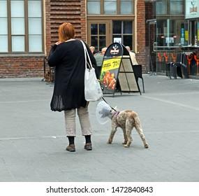 FINLAND, HELSINKI - JUNE 29, 2019: Helsinki Central railway station. Woman with dog wearing an Elizabethan collar