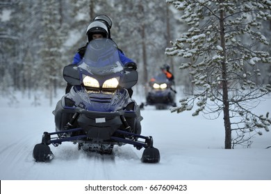 FINLAND - INARI - Caravan of tourists with snowmobiles on the snow - snowcat in North Pole