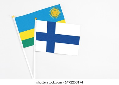 Finland and Rwanda stick flags on white background. High quality fabric, miniature national flag. Peaceful global concept.White floor for copy space.