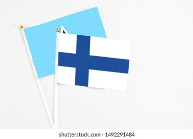 Finland and Saint Lucia stick flags on white background. High quality fabric, miniature national flag. Peaceful global concept.White floor for copy space.