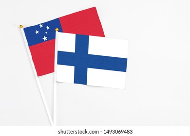 Finland and Samoa stick flags on white background. High quality fabric, miniature national flag. Peaceful global concept.White floor for copy space.