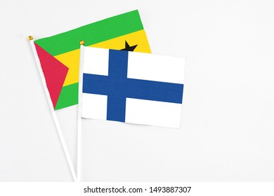 Finland and Sao Tome And Principe stick flags on white background. High quality fabric, miniature national flag. Peaceful global concept.White floor for copy space.