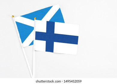 Finland and Scotland stick flags on white background. High quality fabric, miniature national flag. Peaceful global concept.White floor for copy space.