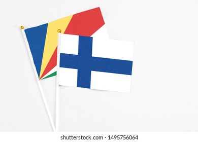 Finland and Seychelles stick flags on white background. High quality fabric, miniature national flag. Peaceful global concept.White floor for copy space.v