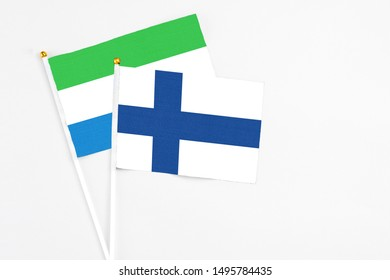 Finland and Sierra Leone stick flags on white background. High quality fabric, miniature national flag. Peaceful global concept.White floor for copy space.