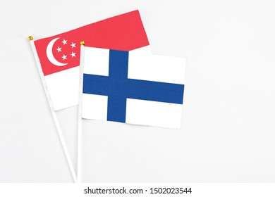 Finland and Singapore stick flags on white background. High quality fabric, miniature national flag. Peaceful global concept.White floor for copy space.