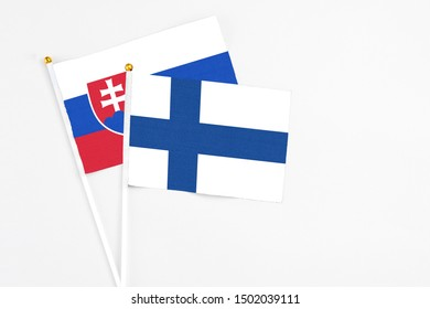 Finland and Slovakia stick flags on white background. High quality fabric, miniature national flag. Peaceful global concept.White floor for copy space.
