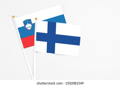 Finland and Slovenia stick flags on white background. High quality fabric, miniature national flag. Peaceful global concept.White floor for copy space.