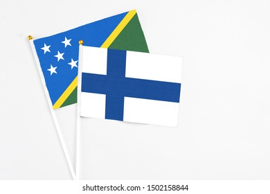 Finland and Solomon Islands stick flags on white background. High quality fabric, miniature national flag. Peaceful global concept.White floor for copy space.