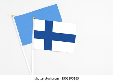 Finland and Somalia stick flags on white background. High quality fabric, miniature national flag. Peaceful global concept.White floor for copy space.