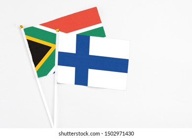 Finland and South Africa stick flags on white background. High quality fabric, miniature national flag. Peaceful global concept.White floor for copy space.