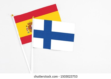 Finland and Spain stick flags on white background. High quality fabric, miniature national flag. Peaceful global concept.White floor for copy space.
