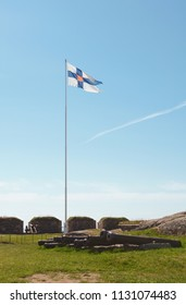 Finland state flag flying high on a flagpole on Suomenlinna sea fortress. A row of disused cannons lies below on the grass.
