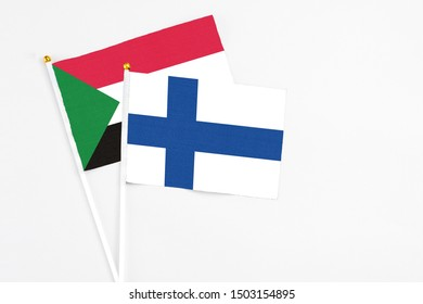 Finland and Sudan stick flags on white background. High quality fabric, miniature national flag. Peaceful global concept.White floor for copy space.