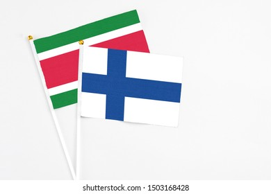 Finland and Suriname stick flags on white background. High quality fabric, miniature national flag. Peaceful global concept.White floor for copy space.