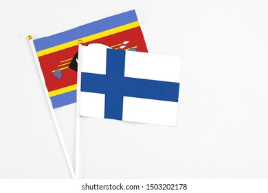 Finland and Swaziland stick flags on white background. High quality fabric, miniature national flag. Peaceful global concept.White floor for copy space.
