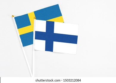 Finland and Sweden stick flags on white background. High quality fabric, miniature national flag. Peaceful global concept.White floor for copy space.