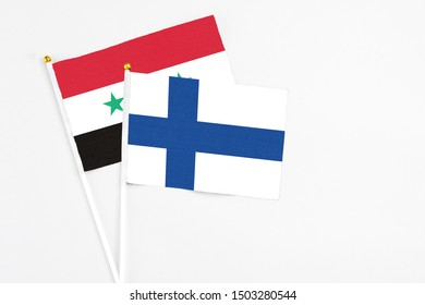 Finland and Syria stick flags on white background. High quality fabric, miniature national flag. Peaceful global concept.White floor for copy space.