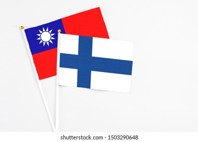 Finland and Taiwan stick flags on white background. High quality fabric, miniature national flag. Peaceful global concept.White floor for copy space.