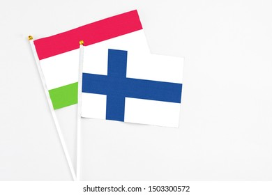 Finland and Tajikistan stick flags on white background. High quality fabric, miniature national flag. Peaceful global concept.White floor for copy space.
