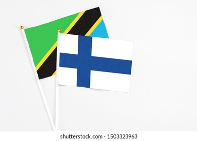 Finland and Tanzania stick flags on white background. High quality fabric, miniature national flag. Peaceful global concept.White floor for copy space.