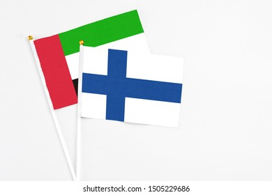 Finland and United Arab Emirates stick flags on white background. High quality fabric, miniature national flag. Peaceful global concept.White floor for copy space.