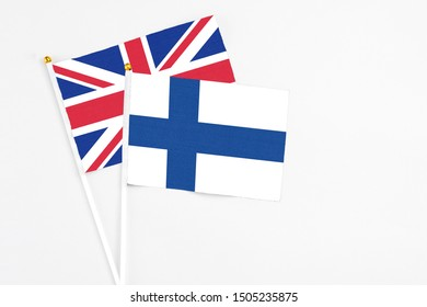Finland and United Kingdom stick flags on white background. High quality fabric, miniature national flag. Peaceful global concept.White floor for copy space.