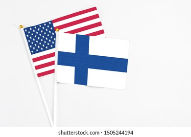 Finland and United States stick flags on white background. High quality fabric, miniature national flag. Peaceful global concept.White floor for copy space.