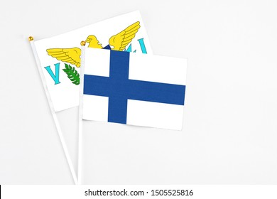 Finland and United States Virgin Islands stick flags on white background. High quality fabric, miniature national flag. Peaceful global concept.White floor for copy space.