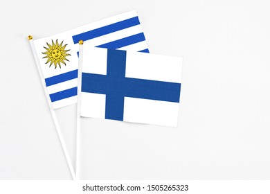 Finland and Uruguay stick flags on white background. High quality fabric, miniature national flag. Peaceful global concept.White floor for copy space.