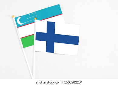 Finland and Uzbekistan stick flags on white background. High quality fabric, miniature national flag. Peaceful global concept.White floor for copy space.