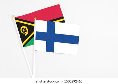 Finland and Vanuatu stick flags on white background. High quality fabric, miniature national flag. Peaceful global concept.White floor for copy space.