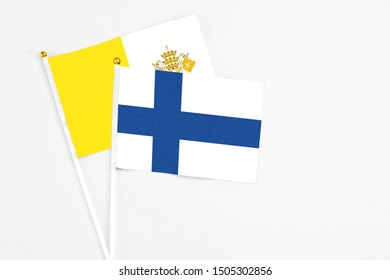 Finland and Vatican City stick flags on white background. High quality fabric, miniature national flag. Peaceful global concept.White floor for copy space.