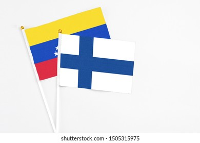 Finland and Venezuela stick flags on white background. High quality fabric, miniature national flag. Peaceful global concept.White floor for copy space.