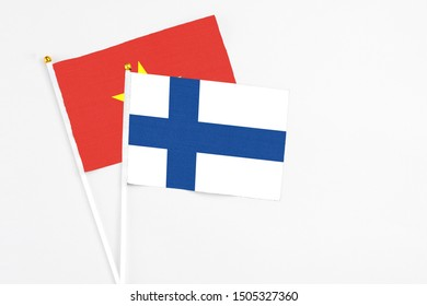 Finland and Vietnam stick flags on white background. High quality fabric, miniature national flag. Peaceful global concept.White floor for copy space.