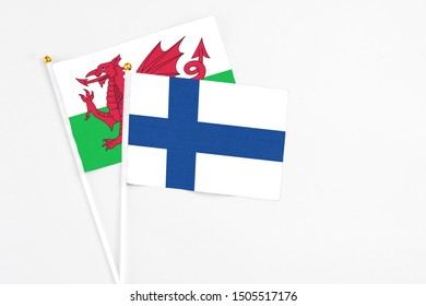 Finland and Wales stick flags on white background. High quality fabric, miniature national flag. Peaceful global concept.White floor for copy space.