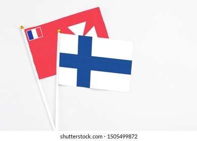 Finland and Wallis And Futuna stick flags on white background. High quality fabric, miniature national flag. Peaceful global concept.White floor for copy space.