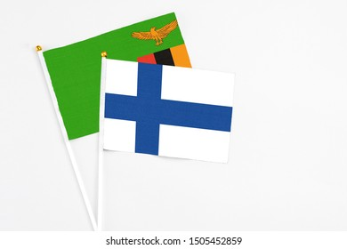 Finland and Zambia stick flags on white background. High quality fabric, miniature national flag. Peaceful global concept.White floor for copy space.