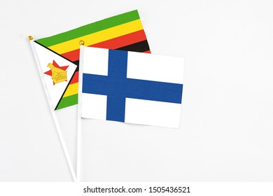 Finland and Zimbabwe stick flags on white background. High quality fabric, miniature national flag. Peaceful global concept.White floor for copy space.