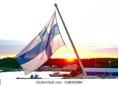 Finnish flag against the setting sun, in the evening at the port of Turku, Finland