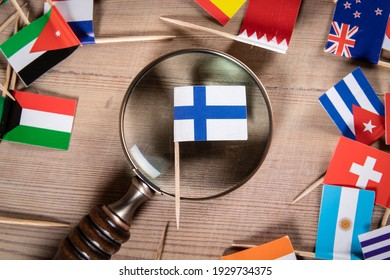 Finnish flag. Economic growth, Imports and Exports, Armaments and Security concept. Magnifying glass and flags of different countries