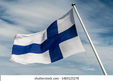 The Finnish flag flutters in the wind against the Sunny sky with big feathery clouds