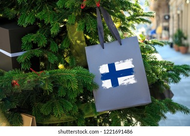 Finnish flag printed on a Christmas shopping bag. Close up of a shopping bag as a decoration on a Xmas tree on a street in Finland Suomi . Christmas shopping, local market sale and deals concept.