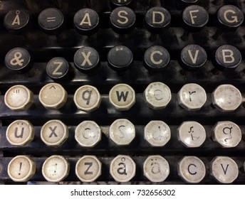Finnish grungy old vintage typewriter including uppercase and lowercase letter Å with ring, letters Ä and Ü with diaereses, combining diaeresis (¨), QWERTY, and ASDF keys.