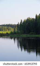 Finnish lake in summer day with mirror in water and forest. Vertical photo.