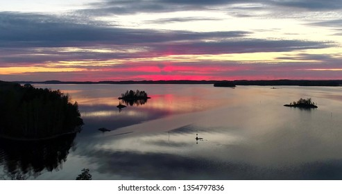 Finnish lake at sunset, aerial, drone shot of a colorful, red sundown, above islands and the reflecting water of haapavesi, on a sunny evening dusk,near Savonlinna in north Karelia, Finland