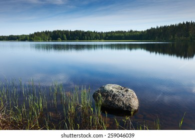 Finnish lake with trees in the background and a big rock in the foreground